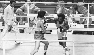 FILE - In this July 29, 1976, file phot, Sugar Ray Leonard of Palmer Park, Md., right, throws a right at Kazmier Szczerba of Poland during the light welterweight boxing match at the XXI Summer Olympic Games in Montreal, Quebec, Canada. (AP Photo/File)
