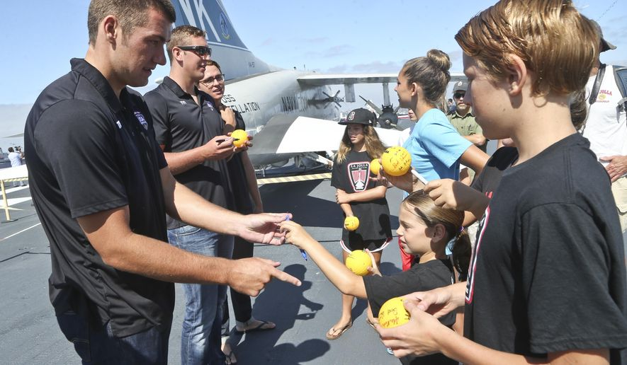 The United States Men's Olympic Water Polo team signs autographs for young fans on the deck of the USS Midway Museum where they were formerly introduced Thursday, July 7, 2016, in San Diego. (AP Photo/Lenny Ignelzi)