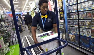 Tracey Anderson, 26, restocks X-Box sets on opening day of a new Wal-Mart on Georgia Avenue in northwest D.C. on Dec. 4, 2013. (Associated Press) **FILE**