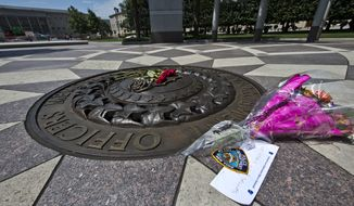 Five red roses on the bronze medallion with another bouquet of flowers and a note in support of the Dallas Police Department are seen at The National Law Enforcement Officers Memorial in Washington, Friday, July 8, 2016. Five law enforcement officers were killed in Dallas on Thursday. (AP Photo/Alex Brandon)