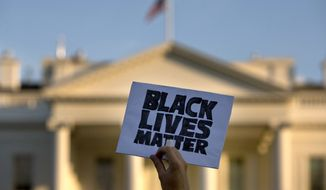 "A man holds up a sign saying ""black lives matter"" during a protest of shootings by police, in Washington, Friday, July 8, 2016, by the White House. In the span of four days, the United States has had to come to terms with the deaths of two black men at the hands of police - the first caught on video and the aftermath of the second livestreamed on Facebook - as well as the deadliest day for U.S. law enforcement since 9/11. (AP Photo/Jacquelyn Martin)"