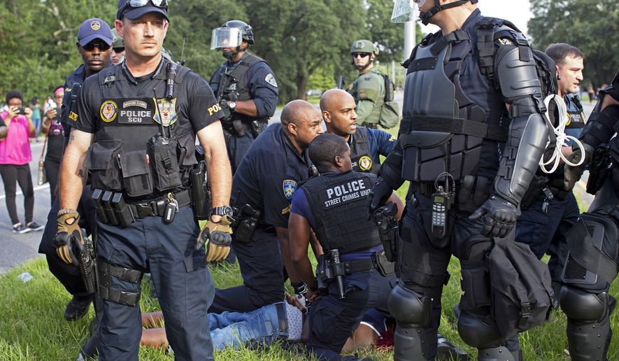 Police arrest a protester in front of the Baton Rouge Police Department headquarters after police attempted to clear protesters from the street in Baton Rouge, La., Saturday, July 9, 2016. Several protesters were arrested. (AP Photo/Max Becherer)