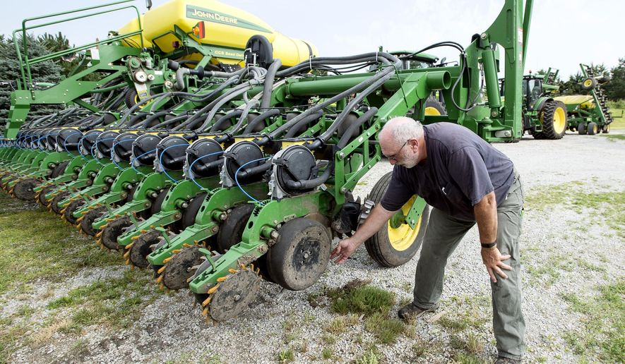 Farmer Mick Minchow takes a look at the fine components of his John Deere planter on Monday, June 20, 2016, at his farm in Waverly, Neb. (Kristin Streff/Lincoln Journal Star via AP)