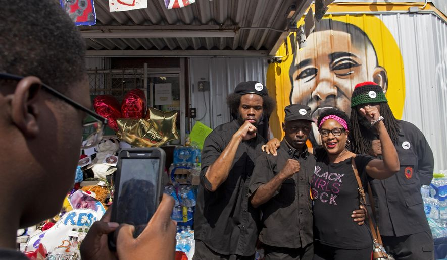 People pose for photographs with members of the New Black Panther party after they announced their intent to protest the death of Alton Sterling at the Baton Rouge Police Department Headquarters in Baton Rouge, Saturday, July 9, 2016. Protests were planned all over Baton Rouge by groups demanding justice for Alton Sterling, a black man killed by police. (AP Photo/Max Becherer)