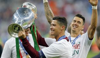 Portugal's Cristiano Ronaldo, centre, celebrates with the trophy at the end of the Euro 2016 final soccer match between Portugal and France at the Stade de France in Saint-Denis, north of Paris, Sunday, July 10, 2016. Portugal won the match 1-0. (AP Photo/Michael Probst)