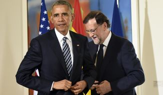 U.S President Barack Obama, left, and Spain's acting Prime Minister Mariano Rajoy stand following their media availability in Madrid, Spain, at the Palacio de la Moncloa, Sunday, July 10, 2016. (AP Photo/Susan Walsh)