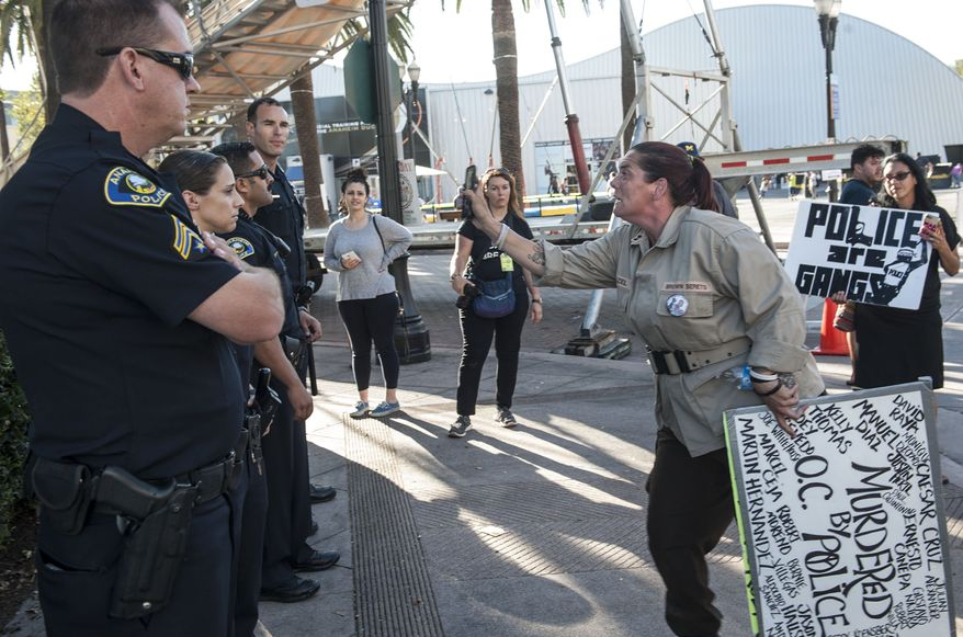 Corie Cline talks to Anaheim police officers during a Black Lives Matter protest in downtown Anaheim, Calif., Sunday, July 10, 2016. Her brother Joe Whitehouse was shot and killed by Anaheim police officers in 2007. The protest started outside Anaheim City Hall on Sunday and dozens of protesters marched to the Police Department. (Ana Venegas/The Orange County Register via AP) A Black Lives Matter protest was held outside  Anaheim City Hall and swelled up to about 75 people who marched to the Anaheim Police Department and through the Eid Festival.