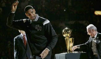 FILE - In this Oct. 28, 2014, file photo, San Antonio Spurs' Tim Duncan, left, holds up his 2014 NBA championship ring during a ceremony prior to an NBA basketball game between the Spurs and the Dallas Mavericks, in San Antonio. Duncan announced his retirement on Monday, July 11, 2016, after 19 seasons, five championships, two MVP awards and 15 All-Star appearances. It marks the end of an era for the Spurs and the NBA. (AP Photo/Eric Gay, File)
