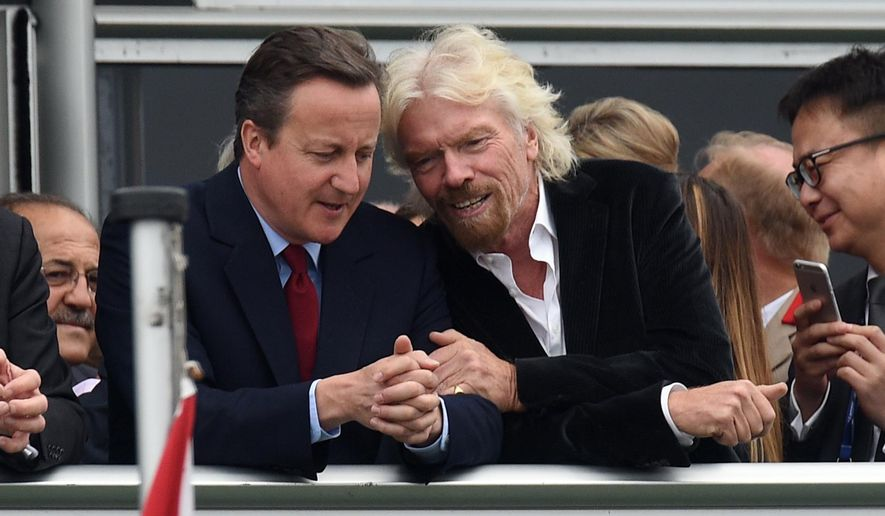 Britain's Prime Minister David Cameron, left, and Virgin boss Richard Branson talk at the Farnborough International Airshow in Farnorough, south England, Monday July 11, 2016.  Britain has signed a contract for nine new P-8A Poseidon military aircraft, and Boeing announced Monday a planned expansion for its British operation, as the airshow attracts large international companies to announce their latest plans. (Andrew Matthews / PA via AP)