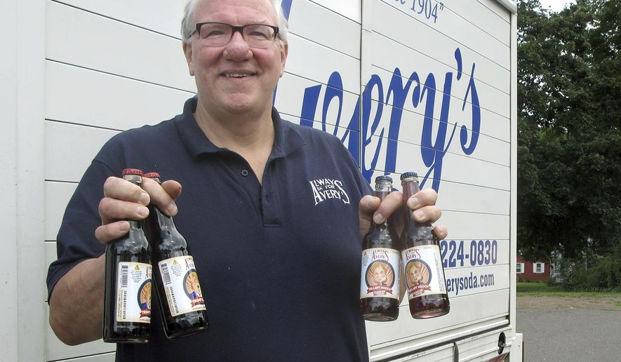 Rob Metz, general manager of Avery's Beverages, holds samples of the company's latest specialty sodas, Hillary Hooch and Trump Tonic, outside the Avery's bottling facility, Monday, July 11, 2016, in New Britain, Conn. This is the third presidential race that company created candidate-based sodas and held a straw poll based on sales. During the last two cycles, Barack O'Berry beat John McCream and Cream de Mitt. (AP Photo/Pat Eaton-Robb)