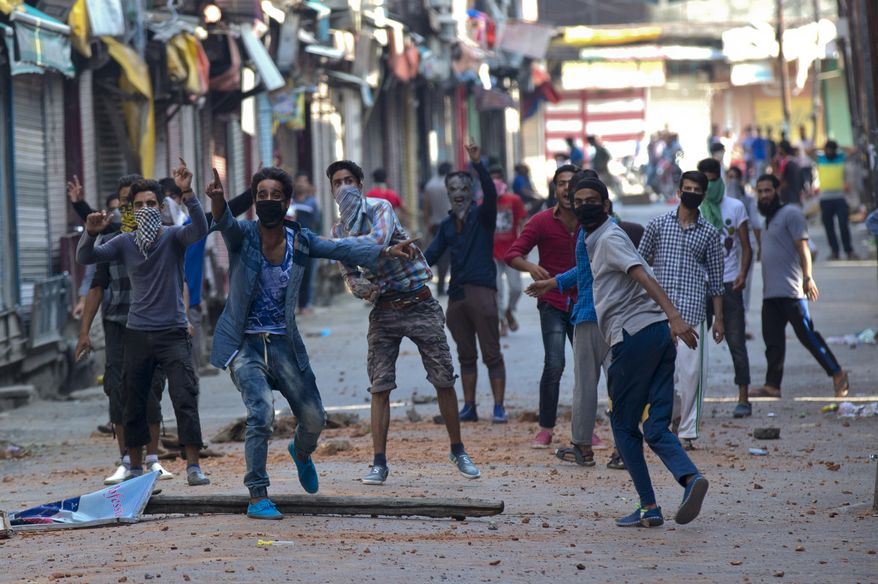 Kashmiri Muslim protesters taunt Indian policemen as they clash in Srinagar, Indian controlled Kashmir, Monday, July 11, 2016. Indian authorities were struggling Monday to contain protests by Kashmiris angry after several people were killed in weekend demonstrations, as youths defied a curfew to rally in the streets against the killing of a top anti-India rebel leader. (AP Photo/Dar Yasin)