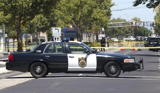 Crime scene tape surrounds the area as Sacramento Police officers investigate the fatal shooting of a knife-waving suspect by police, Monday, July 11, 2016, in Sacramento, Calif. Police were called to the area by witnesses who reported a man walking down the street waving a knife over his head, and that he had a gun in his waistband. When confronted by officers the man allegedly turned toward them with the knife and was shot by police. (AP Photo/Rich Pedroncelli)