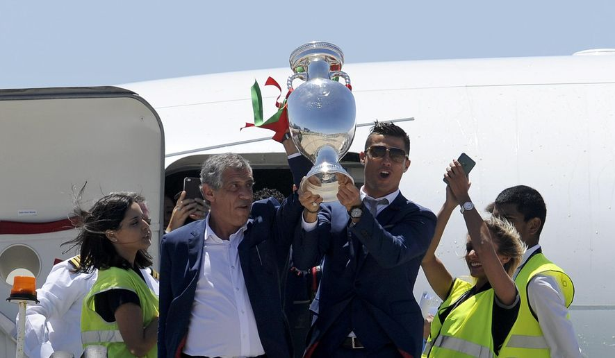 Portugal's Cristiano Ronaldo and coach Fernando Santos, left, lift the Euro 2016 trophy after defeating France in the final, as they arrive at the Humberto Delgado Airport in Lisbon, Portugal, Monday, July 11, 2016. (AP Photo/Paulo Duarte)