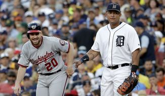 American League's Miguel Cabrera, of the Detroit Tigers, right, holds the pants of National League's Daniel Murphy, of the Washington Nationals, as he takes a lead during the seventh inning of the MLB baseball All-Star Game, Tuesday, July 12, 2016, in San Diego. (AP Photo/Gregory Bull)