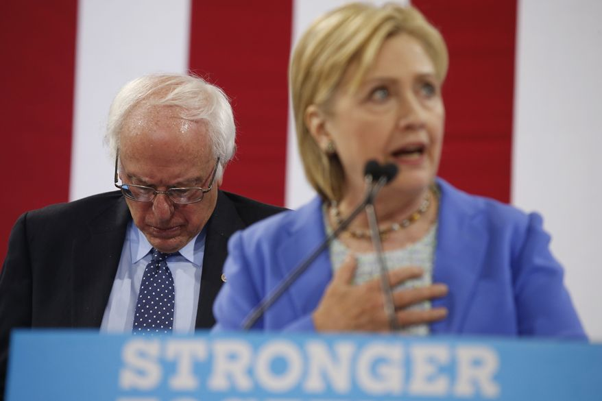Sen. Bernie Sanders, I-Vt. listens as Democratic presidential candidate Hillary Clinton speaks during a rally in Portsmouth, N.H., Tuesday, July 12, 2016, where Sanders endorsed Clinton for president. (AP Photo/Andrew Harnik)