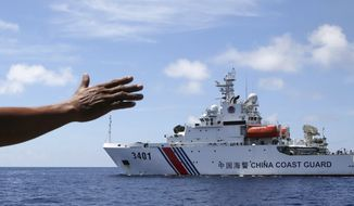 In this photo taken March 29, 2014, Philippines navy personnel motions towards a Chinese Coast Guard to make way as they block them from entering Second Thomas Shoal in the South China Sea. The Permanent Court of Arbitration (PCA) issued its ruling Tuesday, July 12, 2016, in The Hague in response to an arbitration case brought by the Philippines against China regarding the South China Sea, saying that any historic rights to resources that China may have had were wiped out if they are incompatible with exclusive economic zones established under a U.N. treaty. (AP Photo/Bullit Marquez)