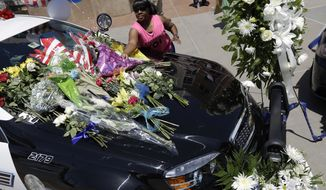 FILE - In this Friday, July 8, 2016 file photo, Cynthia Ware places flowers on a make-shift memorial at the Dallas police headquarters, in Dallas. Five police officers are dead and several injured following a shooting in downtown Dallas Thursday night. Are Black Lives Matter and Blue Lives Matter mutually exclusive? Theoretically, no. In reality, it's looking more like it every day. (AP Photo/Eric Gay, File)