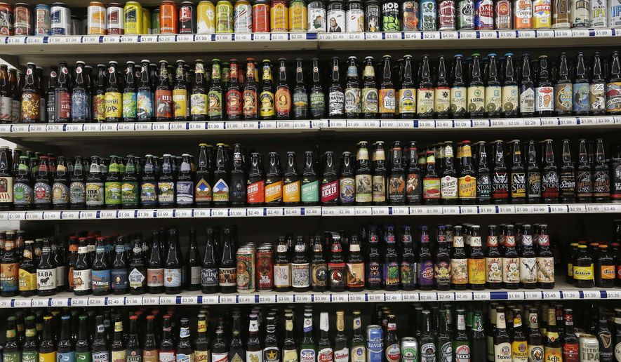 FILE - In this June 9, 2016, file photo, a shelf is stocked high with hundreds of varieties of single beers at Liquor Mart in Boulder, Colo. The Beer Institute says it is encouraging its members to start displaying more product information on labels, packaging and websites in a push to provide consumers with more details about ingredients, calories and other nutritional facts about their beverages. (AP Photo/Brennan Linsley, File)