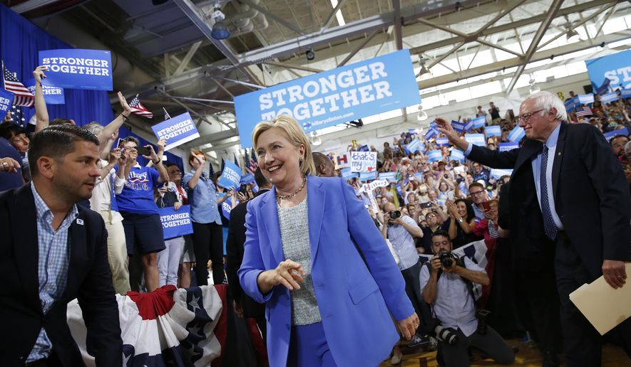 Democratic presidential candidate Hillary Clinton, followed by Sen. Bernie Sanders, I-Vt. arrives for a rally in Portsmouth, N.H., Tuesday, July 12, 2016. (AP Photo/Andrew Harnik)n