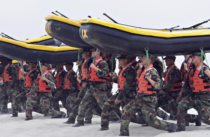 FILE - In this May 14, 2009 file photo, Navy SEAL trainees carry inflatable boats at the Naval Amphibious Base Coronado in Coronado, Calif. In a highly unusual move, the training death of an aspiring Navy SEAL, 21-year-old Seaman James Derek Lovelace, has been ruled a homicide by the San Diego County Medical Examiner. Lovelace was in his first week of training in Coronado, Calif., when he died.  (AP Photo/Denis Poroy, File)