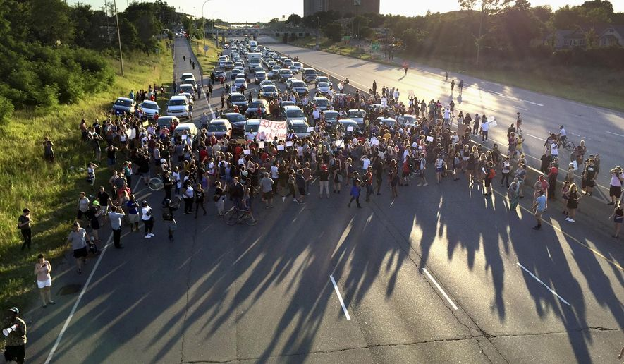 FILE - In this July 9, 2016 file photo, marchers block part of Interstate 94 in St. Paul, Minn., during a protest sparked by the recent police killings of black men in Minnesota and Louisiana. The killing of Philando Castile by a Minnesota police officer during a traffic stop last week tore open wounds that hadn't yet healed in Minnesota's black community from a previous officer-involved death last year. (Glen Stubbe/Star Tribune via AP, File)