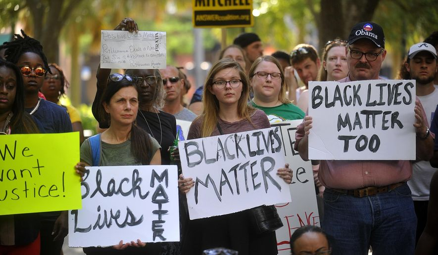 Protesters hold signs during a Black Lives Matter movement protest at Lykes Gaslight Park in downtown Tampa, Fla., Monday, July 11, 2016. (Octavio Jones/Tampa Bay Times via AP)
