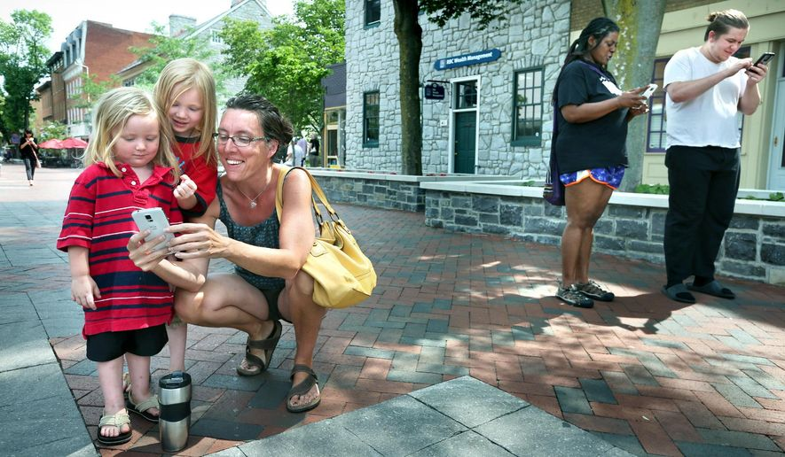 The Loudoun Street Pedestrian Mall in Winchester, Va. is proving a popular spot for people of all ages hunting for Pokemon while playing the popular Pokemon Go game on their cell phones. At left, Melody Schwartzman of Front Royal, Va., collects Pokemon with her sons Liam Schwartzman, 3, and Zach Schwartzman, 5. At right, Danyelle Davis and Steven Hatton, both of Winchester, Va., play the game Tuesday, July 12, 2016. ( Jeff Taylor/The Winchester Star via AP) MANDATORY CREDIT