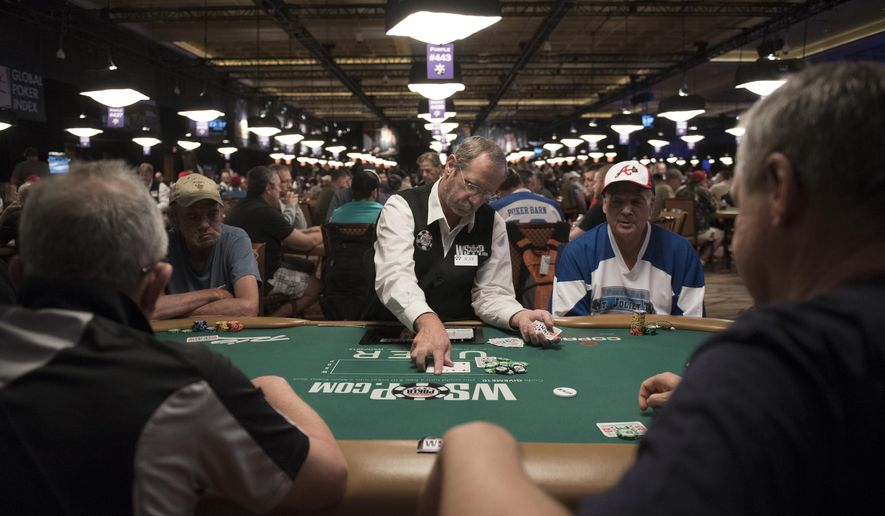 In this photo taken Saturday, July 9, 2016,  Ray Knee, center, deals during Day 1A of the Main Event of the World Series of Poker at the Rio Convention Center in Las Vegas. (Jason Ogulnik/Las Vegas Review-Journal via AP)