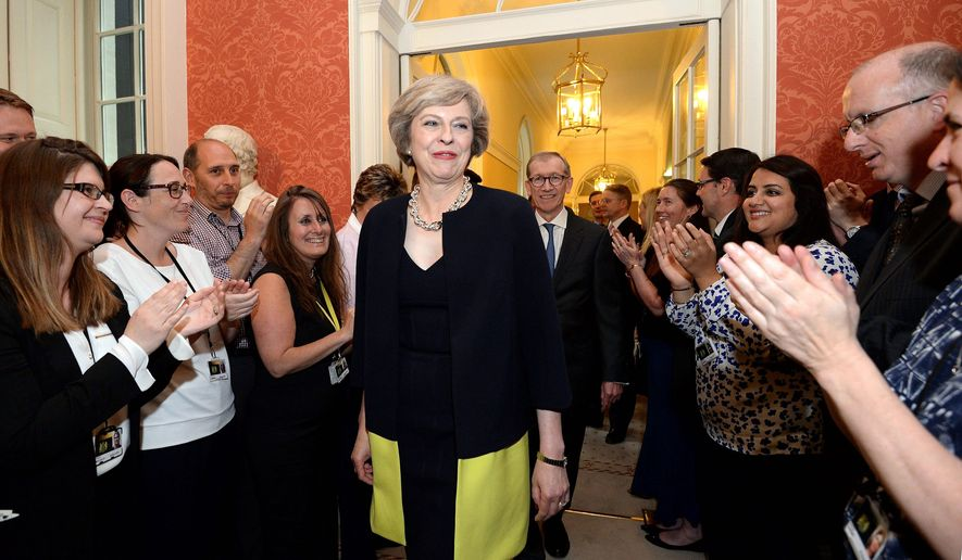 Staff clap as new Prime Minister Theresa May walks into 10 Downing Street, London. David Cameron stepped down Wednesday after six years as prime minister. (Associated Press)