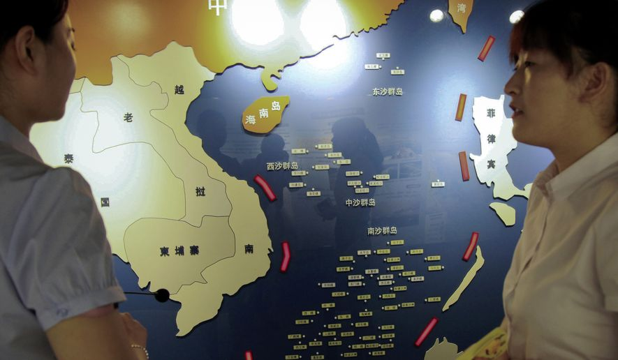 "In this Tuesday, July 12, 2016 photo, workers chat near a map of South China Sea on display at a maritime defense educational facility in Nanjing in east China's Jiangsu province. China blamed the Philippines for stirring up trouble and issued a policy paper Wednesday calling the islands in the South China Sea its ""inherent territory,"" a day after an international tribunal said China had no legal basis for its expansive claims. (Chinatopix via AP)"