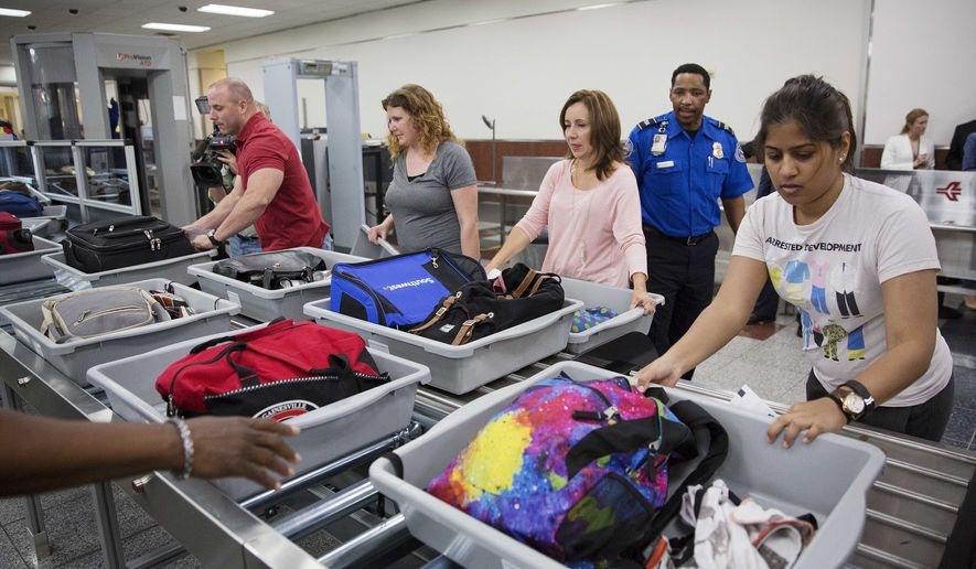Passengers push their carry-on belongings onto an automated conveyer belt at a newly designed passenger screening lane unveiled at Hartsfield-Jackson Atlanta International Airport in Atlanta in this May 2016 file photo. (AP Photo/David Goldman, File) **FILE**