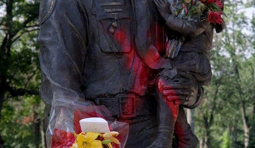 The Richmond Police Memorial statue in Richmond, Va., was vandalized Wednesday, July 12, 2016, with graffiti referring to Alton Sterling, who was killed by a police officer in Baton Rouge, La. The statue was only recently moved to its new location in Byrd Park from the original site in downtown Richmond. ( Bob Brown/Richmond Times-Dispatch via AP)
