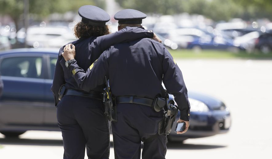 Dallas police officers comfort each other after the funeral services for Dallas Police Sr. Cpl. Lorne Ahrens at Prestonwood Baptist Church on Wednesday in Plano, Texas. (Associated Press)