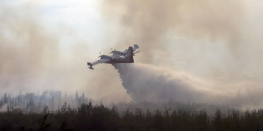 In this photo taken June 18, 2016, and provided by the Alaska Division of Forestry, a CL-415 water scooping aircraft drops its load on the Tetlin River Fire along the Tetlin, Alaska. A year after Alaska wildfires burned an area larger than Massachusetts, the state is on course for a mild fire year in 2016. (Isaac Hofstetter/Alaska Division of Forestry via AP)