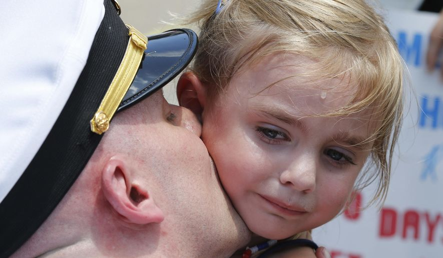 Five-year-old Adley Lausch, cries as she gets a kiss from her father, Lt., Adam Lausch, after he disembarked the nuclear powered aircraft carrier USS Harry S. Truman at Naval Station Norfolk in Norfolk, Va., Wednesday, July 13, 2016. The Truman returns after supporting missions over Iraq and Syria. (AP Photo/Steve Helber)