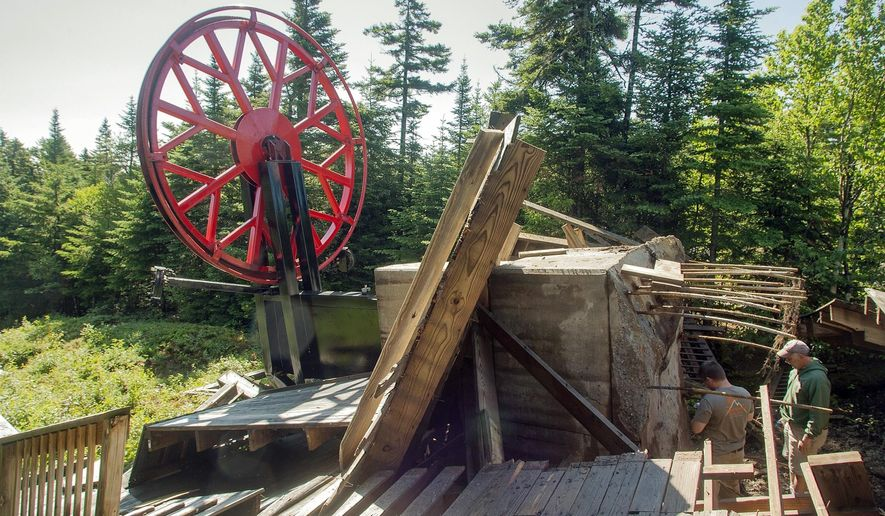 In this Monday, July 11, 2016 photo provided by the Sunday River ski resort, men inspect wreckage of the top unloading terminal of the resort's Spruce Peak Triple ski lift after it detached from the foundation in Newry, Maine. A resort worker first noticed it Sunday evening, and engineers are trying to determine what happened. It was Maine's third major ski resort chairlift failure in six years. The lift was not in operation at the time, and there were no injuries. (Nick Lambert/Sunday River via AP)