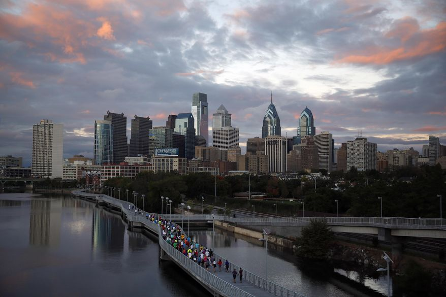 FILE - In this Oct. 1, 2014 file photo, runners jog along the Schuylkill Banks Boardwalk in Philadelphia. Democrats are set to begin their convention at the end of July 2016 in a city that symbolizes both the nation's promise and its shortcomings. (AP Photo/Matt Slocum, File)