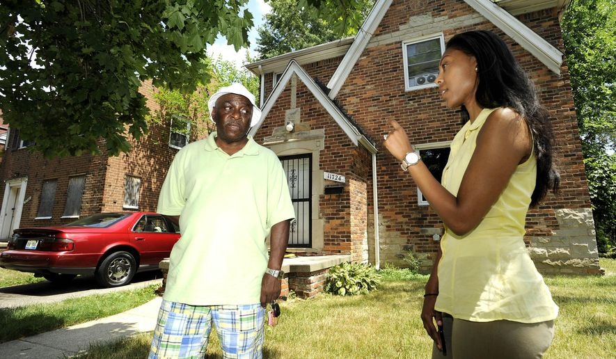 In this photo taken Tuesday, July 12, 2016, homeowner Walter Hicks, left, talks with his ACLU attorney Kimberly Buddin  in front of his house in Detroit. Hicks has been taxed as if his home was worth $40,000 when a recent appraisal priced it at $9,000. An ACLU of Michigan lawsuit expected to be filed Wednesday, July 13, wants to stop the annual tax foreclosure sale in Wayne County until Detroit officials correct inflated assessments.  (Todd McInturf/Detroit News via AP)