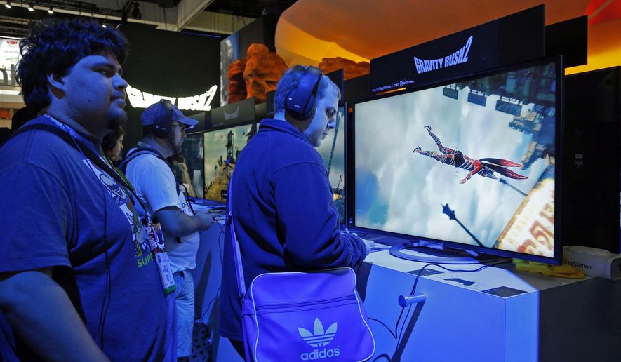 "FILE - In this June 15, 2016 file photo,  a spectator watches players trying out the PlayStation ""Gravity Rush 2"" video game at the Electronic Entertainment Expo in Los Angeles. The boost in sales from viewers watching online streaming video isn't merely changing how game makers market and promote their latest creations. It's also reshaping how they design games from the outset. (AP Photo/Nick Ut, File)"