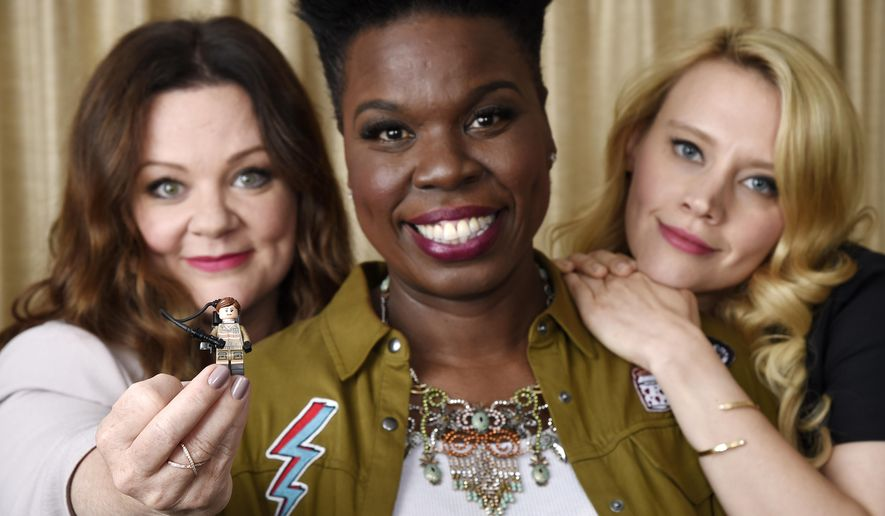 "In this July 8, 2016 photo, Melissa McCarthy, left, Leslie Jones, center, and Kate McKinnon, cast members in ""Ghostbusters,"" pose with a Lego toy figure of fellow cast member Kristen Wiig during a portrait session at the Four Seasons Hotel in Los Angeles. Their film will be released on Friday. (Photo by Chris Pizzello/Invision/AP)"