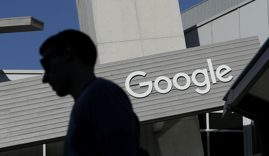 In this Nov. 12, 2015, file photo, a man walks past a building on the Google campus in Mountain View, Calif. Google and LinkedIn said on July 13, 2016, that they have completed a massive land swap involving several Silicon Valley properties. (AP Photo/Jeff Chiu, File)