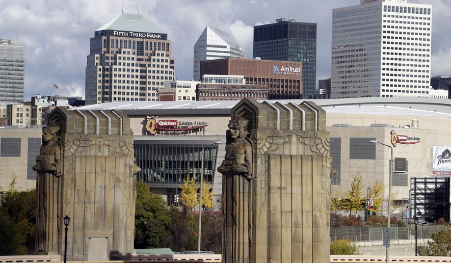 FILE - This Nov. 8, 2013, file photo shows Cleveland's skyline and the venue of the 2016 Republican National Convention, Quicken Loans Arena, framed by the Guardians of Traffic sculptures at the east end of the Hope Memorial Bridge in Cleveland. Donald Trump's effort to unite a splintered Republican Party around his candidacy is about to take center stage in a city that is itself deeply fractured. (AP Photo/Mark Duncan, File)