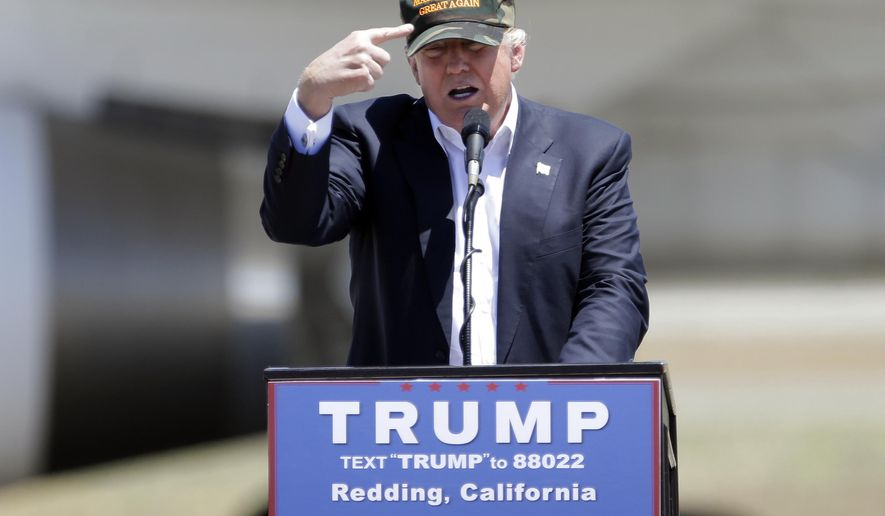 "FILE - In this June 3, 2016 file photo, Republican presidential candidate Donald Trump gestures to a his camouflaged ""Make America Great"" hat at a campaign rally at the Redding Municipal Airport in Redding, Calif. (AP Photo/Rich Pedroncelli, File)"