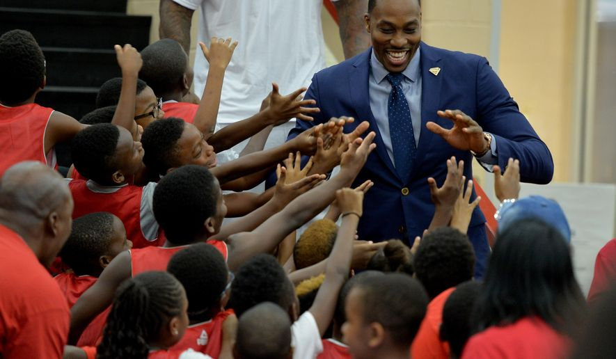 Dwight Howard is greeted by participants in the D12 Foundation basketball camp as he is introduced as the newest member of the Atlanta Hawks at a news conference Wednesday July 13, 2016, in Atlanta. (Brandt Sanderlin/Atlanta Journal-Constitution via AP)