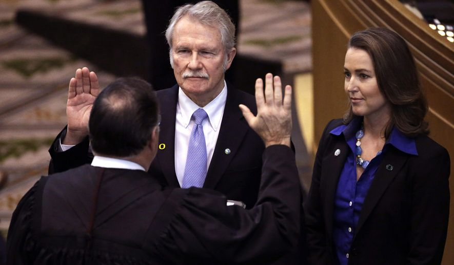 FILE - In this Jan. 12, 2015, file photo, Oregon Gov. John Kitzhaber, left, is joined by his fiancee, Cylvia Hayes, as he is sworn in for an unprecedented fourth term in Salem, Ore. A federal appellate court panel has ruled that a subpoena seeking emails from former Oregon Gov. John Kitzhaber as part of an influence-peddling investigation is too broad. Kitzhaber resigned in 2015 amid suspicion that his fiancee, Cylvia Hayes, used her relationship with him to earn lucrative consulting contracts. (AP Photo/Don Ryan, File)