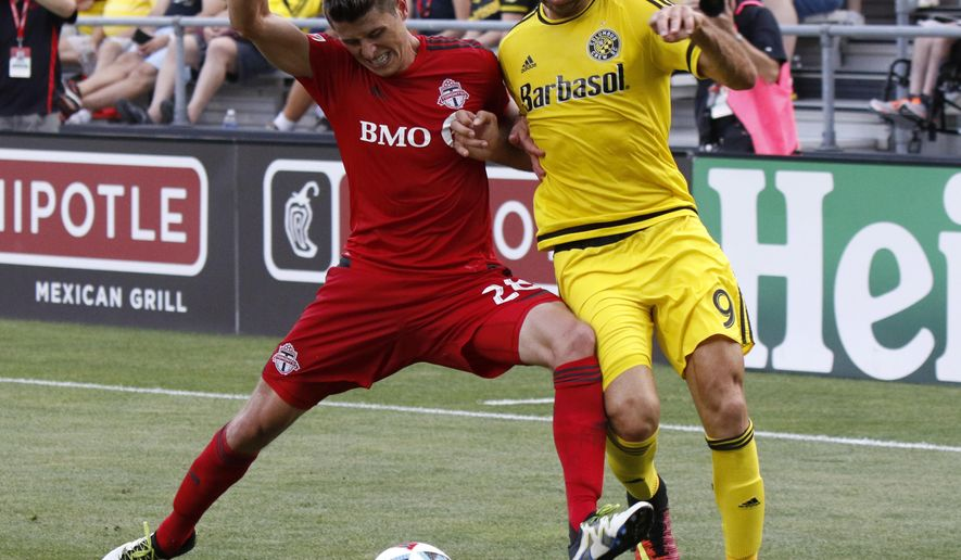 Toronto FC defender Mark Bloom, left, works against Columbus Crew midfielder Justin Meram during the first half of an MLS soccer match in Columbus, Ohio, Wednesday, July 13, 2016. (AP Photo/Paul Vernon)