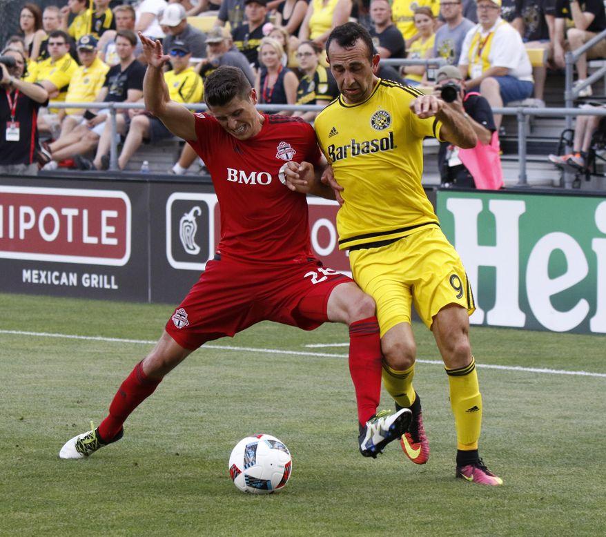 Toronto FC defender Mark Bloom, left, works against Columbus Crew midfielder Justin Meram during the first half of an MLS soccer match in Columbus, Ohio, Wednesday, July 13, 2016. (AP Photo/Paul Vernon)