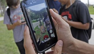 """FILE - In this Tuesday, July 12, 2016, file photo, Pinsir, a Pokemon, is found by a group of Pokemon Go players at Bayfront Park in downtown Miami. The """"Pokemon Go"""" craze has sent legions of players hiking around cities and battling with """"pocket monsters"""" on their smartphones. (AP Photo/Alan Diaz, File)"""