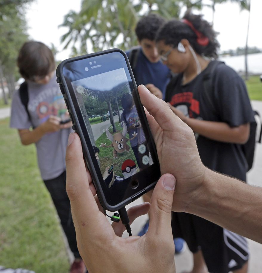 "FILE - In this Tuesday, July 12, 2016, file photo, Pinsir, a Pokemon, is found by a group of Pokemon Go players at Bayfront Park in downtown Miami. The ""Pokemon Go"" craze has sent legions of players hiking around cities and battling with ""pocket monsters"" on their smartphones. (AP Photo/Alan Diaz, File)"