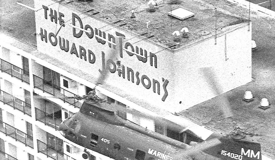 FILE - In this Jan. 8, 1973 file photo, a Marine Corps helicopter makes a pass over the Downtown Howard Johnson Motor Lodge in New Orleans firing at the block house at center where police believe sniper Mark Essex was hiding. Marine Corps Lt. Col. Chuck Pitman piloted the aircraft that carried NOPD Sgt. Antoine Saacks and the NOPD officers that shot Essex. The July 7, 2016 sniper attack in Dallas was gloomily reminiscent of the 1973 shooting spree in downtown New Orleans. The attacker was Mark Essex, a black former military man , who was shot and killed from a helicopter. He harbored deep-seated hatred for whites that people who knew him said took root in the Navy. (AP Photo, File)